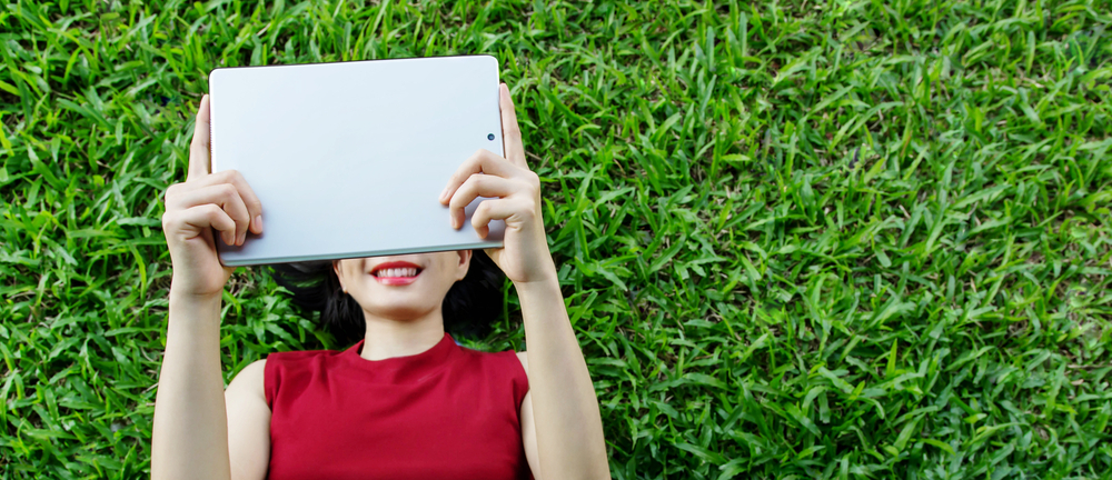 woman on ipad in the grass.jpg